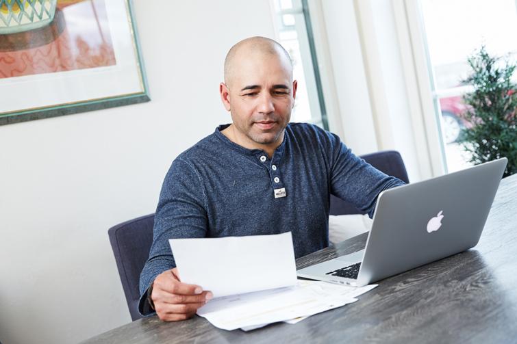 Mann med papirer foran pc. Foto