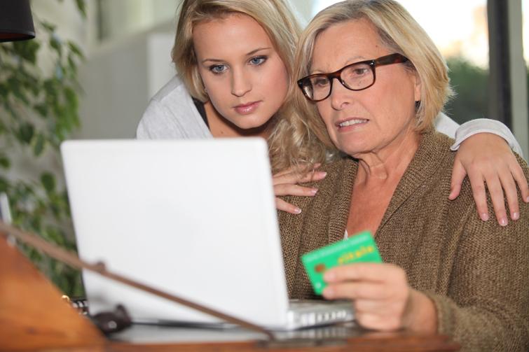 Mor og datter foran pc med kredittkort. Foto