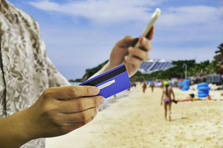 Mann som betaler med kort på stranda. foto.