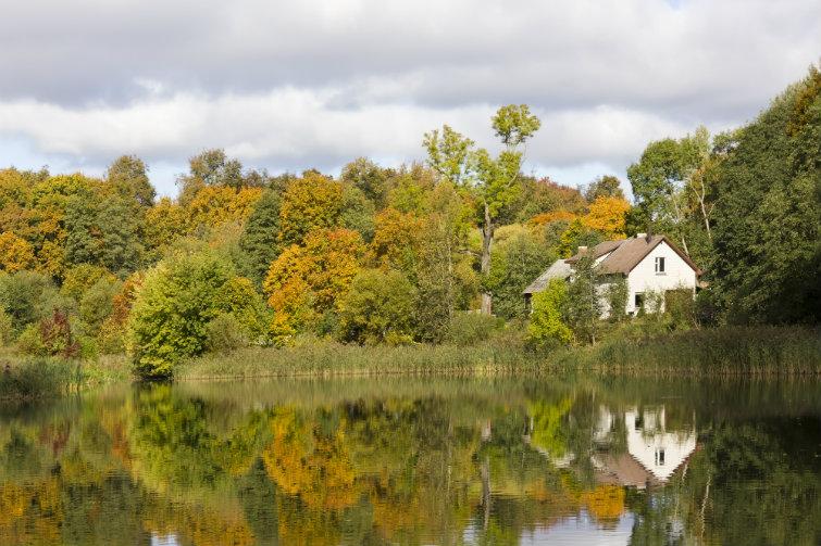 Bilde av hytte ved vannet om høsten. foto.